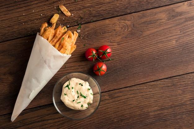 Patate fritte, in un sacchetto di carta su legno