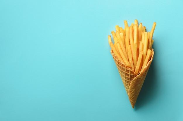 Patate fritte nei coni della cialda su fondo blu. patate fritte salate calde con salsa di pomodoro, foglie di basilico. fast food, cibo spazzatura, concetto di dieta.