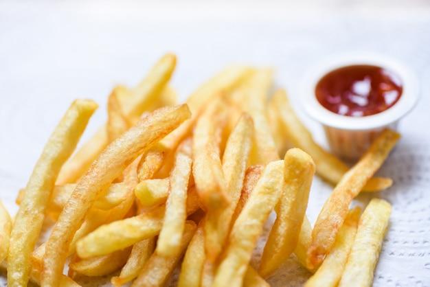 Patate fritte su carta bianca con ketchup sul tavolo da pranzo