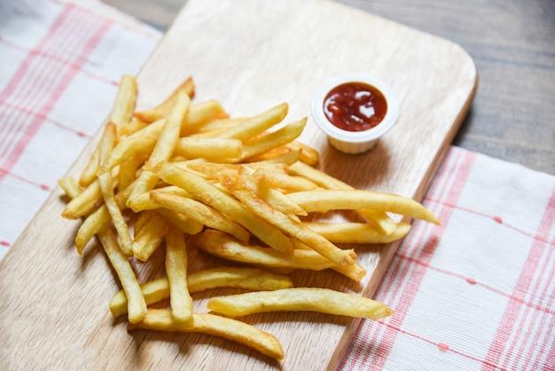 Patate fritte sul bordo di legno con ketchup