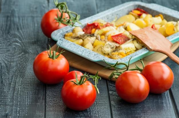 Patate in umido e pomodori maturi su un fondo di legno