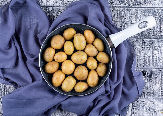 Patate in una padella sul panno viola su una tavola di legno grigia