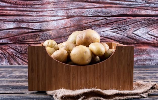 Patate in una scatola di legno su una tavola di legno