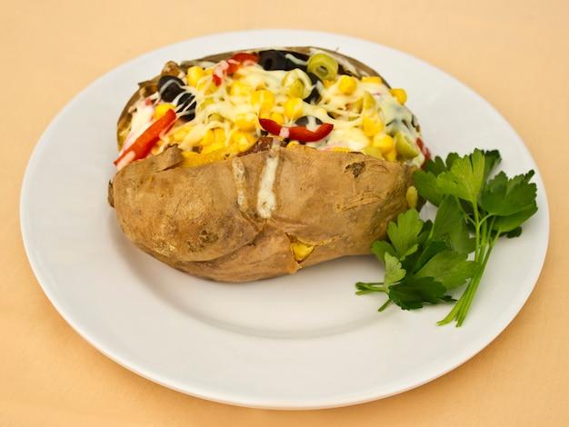 Patate kumpir al forno ripiene di formaggio, salsiccia, olive, peperoni e mais