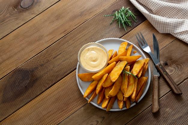 Patatine arrosto con salsa ed erbe.