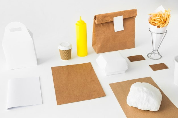 Patatine fritte; bottiglia di salsa; coppa di smaltimento e pacco su superficie bianca
