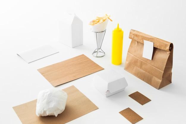 Patatine fritte; bottiglia di salsa e pacco alimentare su sfondo bianco