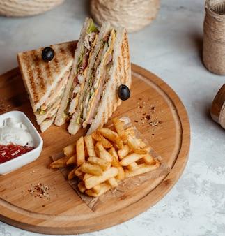 Patatine fritte con sandwich di club servite con salse su una tavola di legno