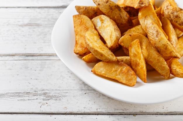 Patatine fritte delle fette di patate sulla tavola di legno