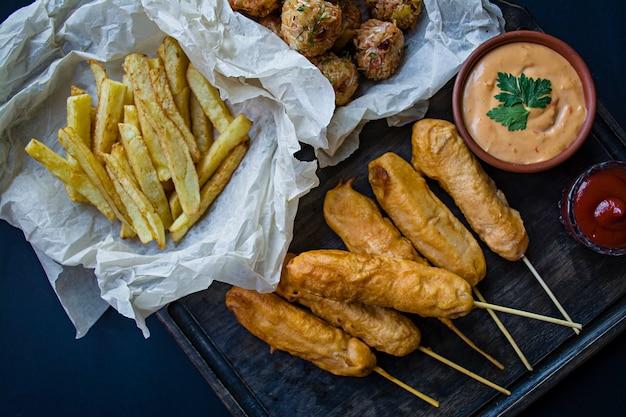 Patatine fritte fritte, corn dog e crocchette di cavolo e patate con salsa e ketchup.
