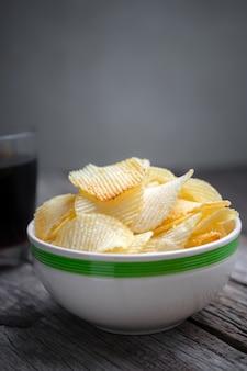 Patatine fritte in ciotola con cola sul fondo della tavola in legno.