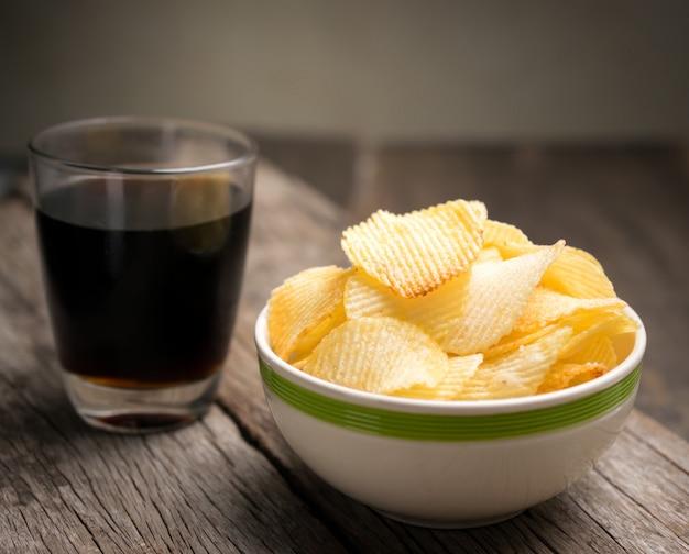 Patatine fritte in ciotola con cola sulla tavola di legno.