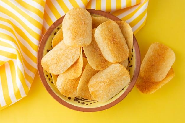 Patatine fritte in ciotola su sfondo giallo, vista dall'alto