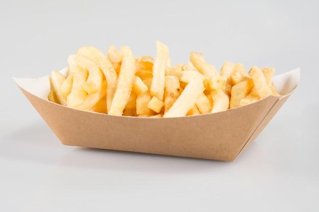 Patatine fritte in scatola di cartone nel piatto da asporto di snack