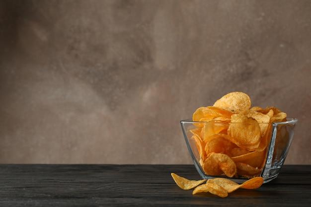 Patatine fritte in una ciotola di vetro sulla tavola di legno, spazio per testo