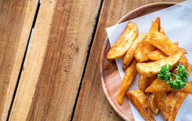Patatine fritte o patate fritte sulla vista del piano d'appoggio di legno, concetto dell'alimento.