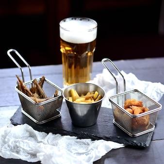 Patatine fritte, pesce fritto e anelli di cipolla in pastella su una tavola di legno, con un bicchiere di birra. spuntini di birra