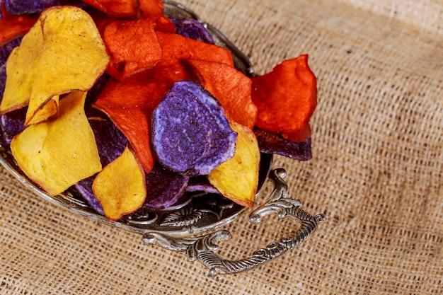 Patatine fritte salate della barbabietola e della carota nelle patatine blu rosse della patata