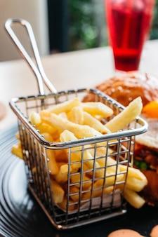 Patatine fritte servite nel cestino di acciaio per mangiare con hamburger.