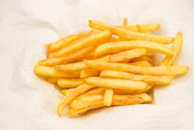 Patatine fritte su carta bianca