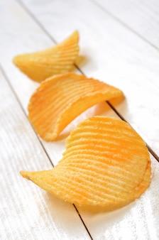 Patatine fritte sulla tavola di legno bianca della plancia
