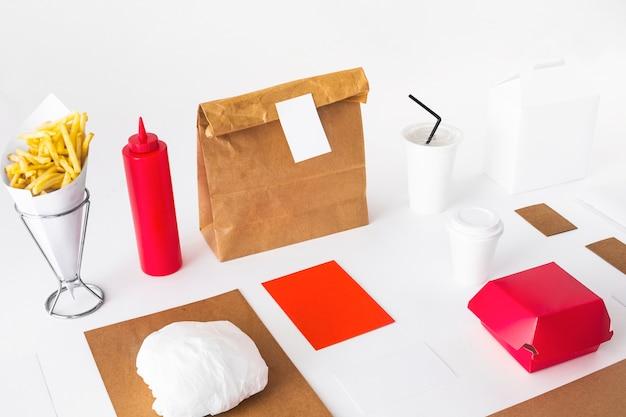 Patatine fritte; tazza di smaltimento; bottiglia di salsa e pacchetti di cibo sul piano del tavolo bianco
