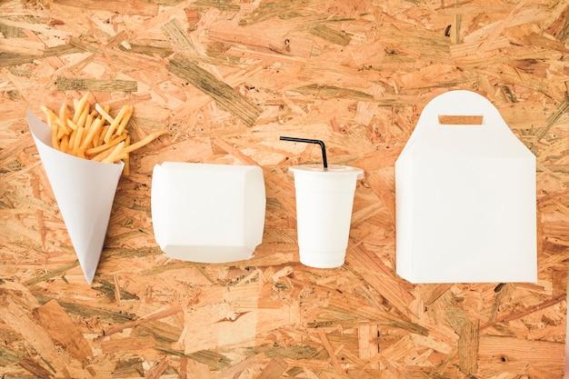 Patatine fritte; tazza di smaltimento e pacchetti in fila sul tavolo di legno