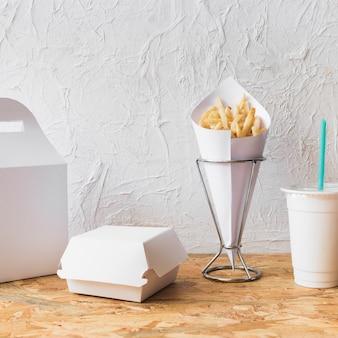 Patatine fritte; tazza di smaltimento e pacco alimentare sulla scrivania in legno