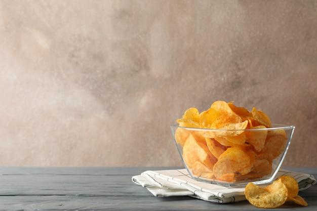 Patatine fritte, tovagliolo sulla tavola di legno grigia su marrone, spazio per testo