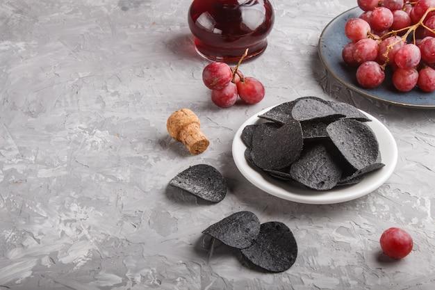 Patatine nere con carbone, aceto balsamico in vetro, uva rossa su un piatto di ceramica blu su una superficie di cemento grigia. vista laterale.
