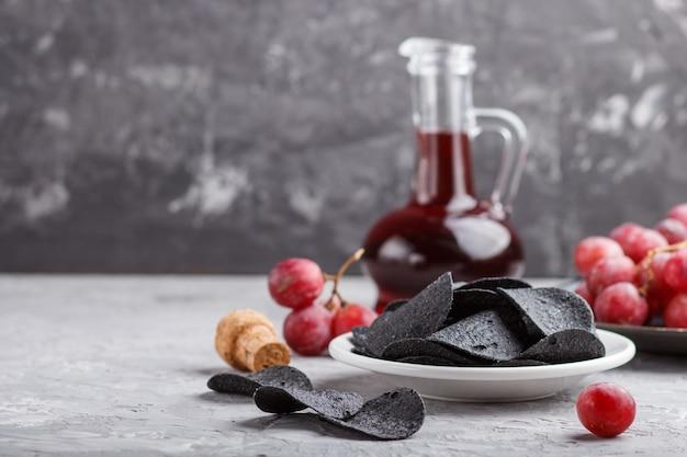 Patatine nere con carbone, aceto balsamico in vetro, uva rossa su un piatto di ceramica blu