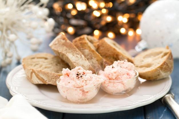 Patè dei frutti di mare con pane sul piatto bianco
