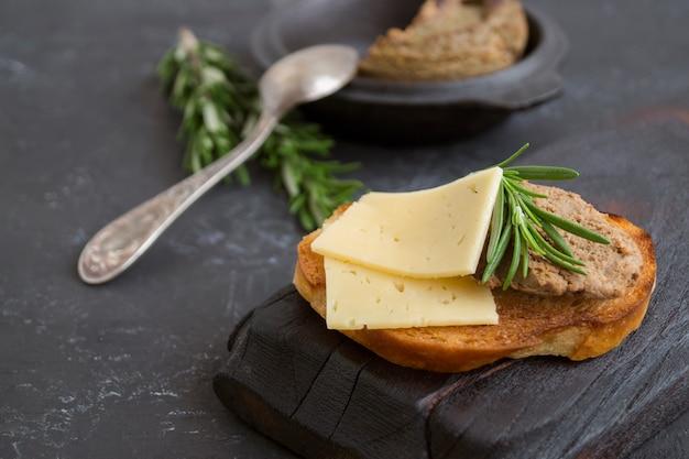Patè di carne fatto in casa su pane croccante tostato. stile fotografico scuro.