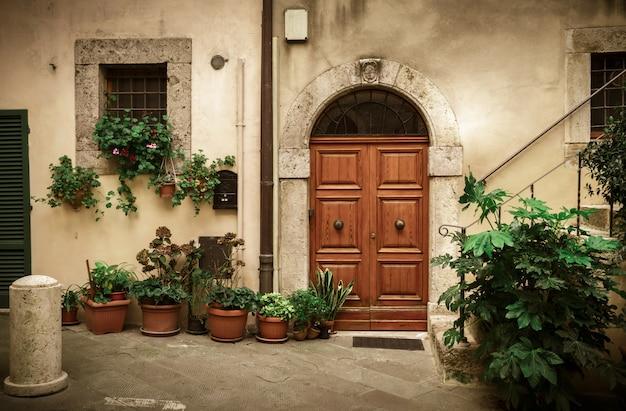 Patio cortile italiano con vecchia porta e vasi di piante