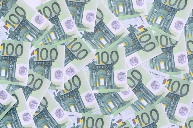 Pattern di sfondo di un insieme di denominazioni monetarie verdi di 100 euro.