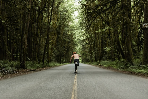 Pattinaggio maschile su una strada deserta in mezzo alla foresta