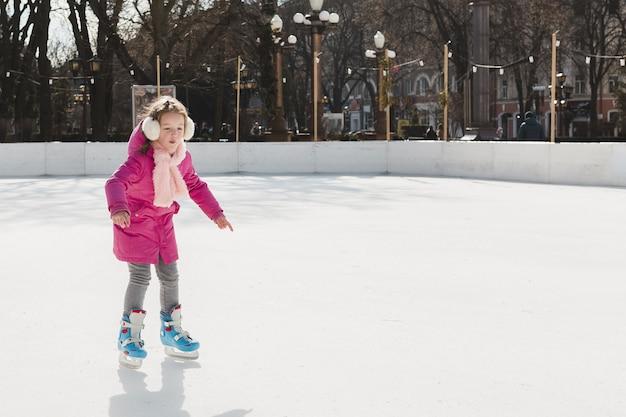 Pattinaggio su ghiaccio adorabile della ragazza all'aperto
