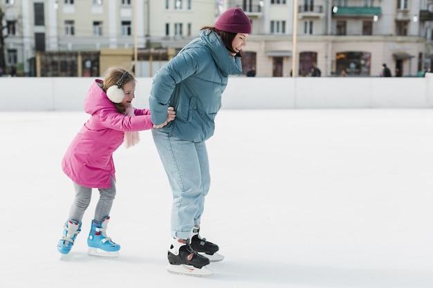 Pattinaggio su ghiaccio felice del bambino e della madre
