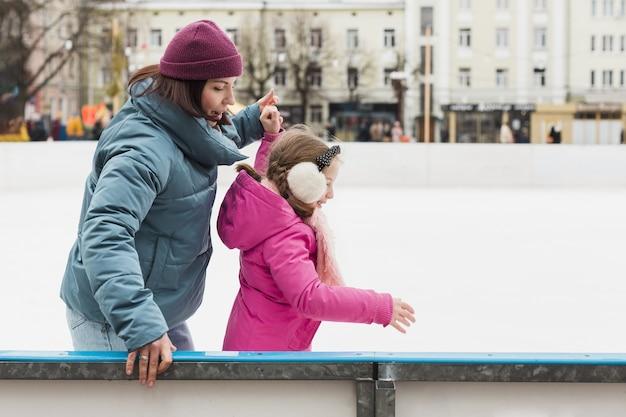 Pattinaggio su ghiaccio sveglio della ragazza e della madre