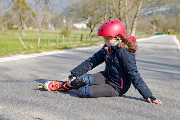 Pattinatore adolescente che fa smorfie nel dolore dopo la caduta