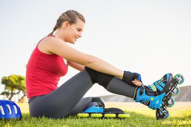 Pattinatore biondo sportivo sorridente che si siede nell'erba