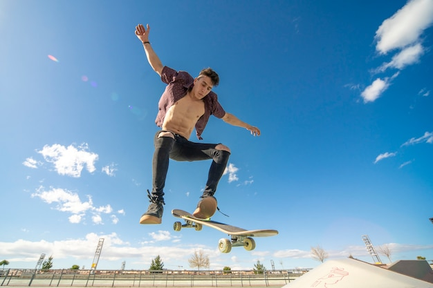 Pattinatore con skateboard facendo trucco nel parco skate