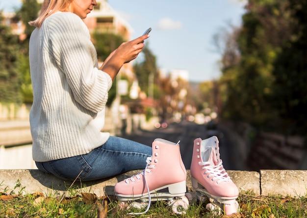 Pattini a rotelle con la donna che esamina smartphone