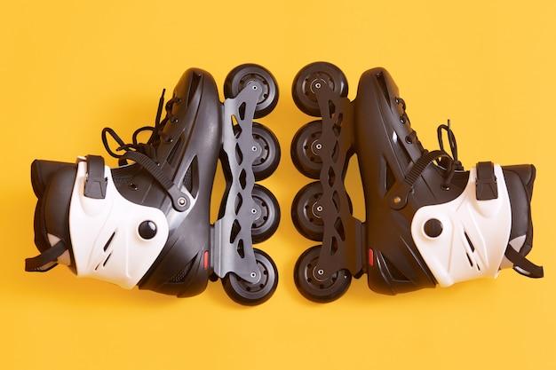 Pattini a rotelle isolati su giallo, coppia di nuovi pattini bianchi e neri freschi, attrezzatura per allenamento sportivo attivo, pista di pattinaggio, pattinaggio, pattinaggio. concetto di riposo attivo.