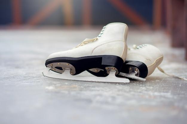 Pattini da ghiaccio bianchi per pattinaggio artistico si trovano su una pista di pattinaggio