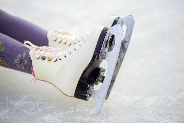 Pattini di figura dei bambini su un primo piano della pista di pattinaggio sul ghiaccio. pattinaggio di figura - sport invernali