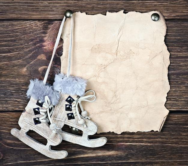 Pattini di figura di legno del giocattolo di natale e un pezzo di carta vecchia