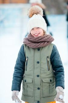 Pattino andante della bambina adorabile nel giorno della neve di inverno all'aperto