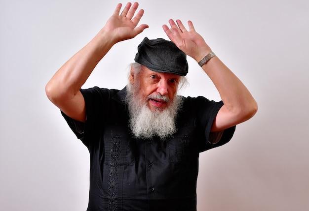 Paura vecchio maschio con la barba che tiene le mani in alto in difesa sotto le luci