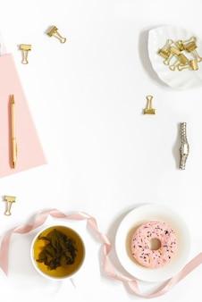 Pausa tè sul posto di lavoro di un libero professionista o di una blogger femmina. donat, tè in una tazza, quaderni, penna su uno sfondo bianco. tendenza blog sfondo con spazio di copia